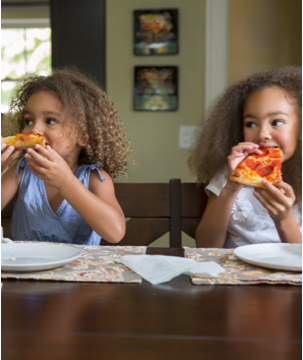 Two little girls happily eating pizza