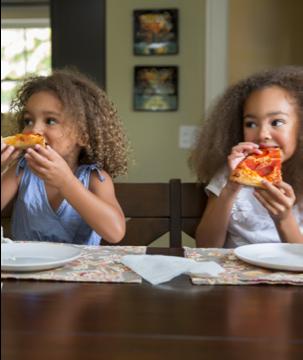 Dos niñas comiendo pizza alegremente
