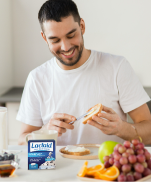 Man eating cream cheese with supplements on the counter