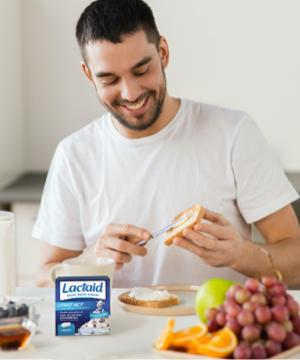 Hombre comiendo queso crema con suplementos sobre encimera